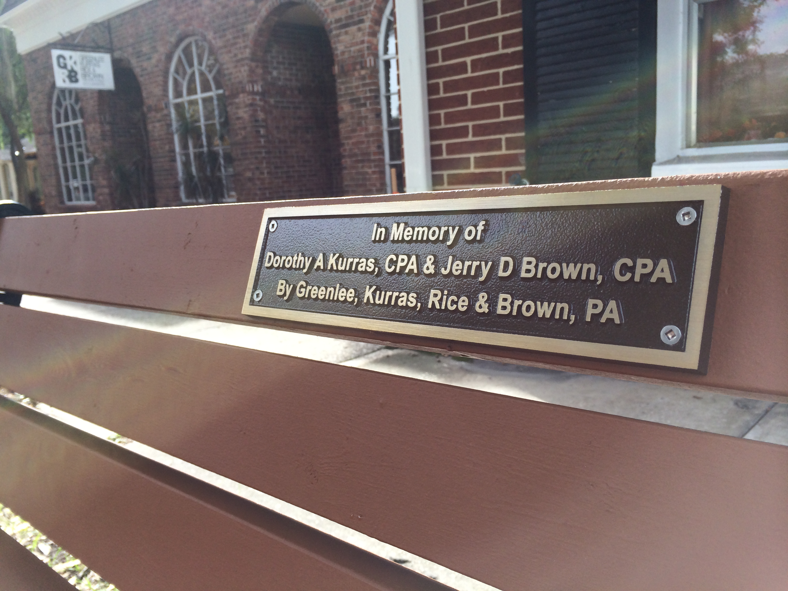 New park bench next to office in memory of firm principals Dottie Kurras CPA (1937-2010) & Jerry Brown CPA (1950-2013)